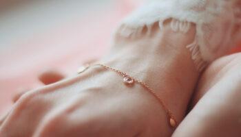 closeup-shot-female-wearing-fashionable-bracelet-with-charm-pendants